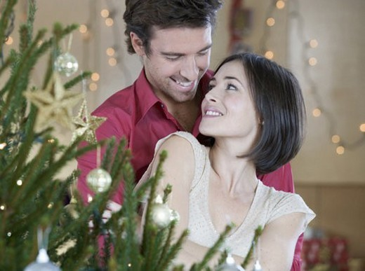 A couple standing by the Christmas tree : Stock Photo