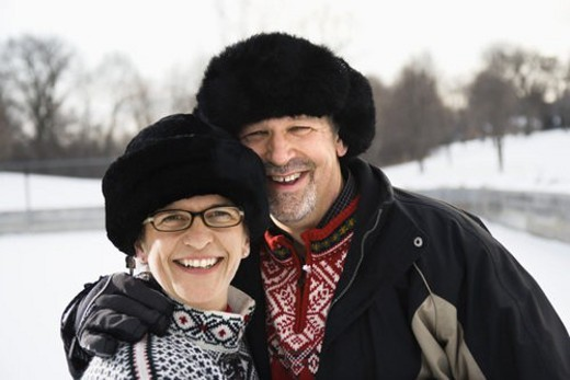 Portrait of Caucasian middle aged man and woman wearing  black winter hats smiling at viewer. : Stock Photo