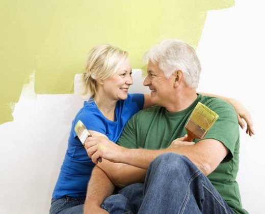 Middle-aged couple snuggling in front of wall they are painting green. : Stock Photo
