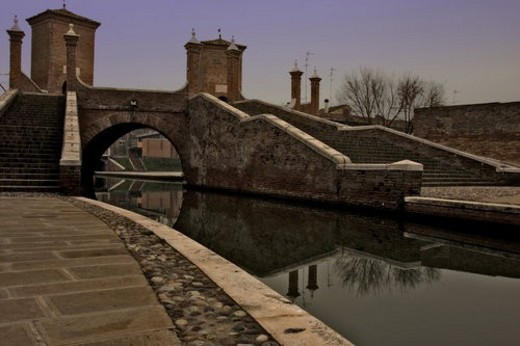 View of 17th century Trepponte red brick bridge, Comacchio, on winter afternoon, showing pavement alongside canals, arches spanning the water, towers, and reflections of pedestrians crossing : Stock Photo