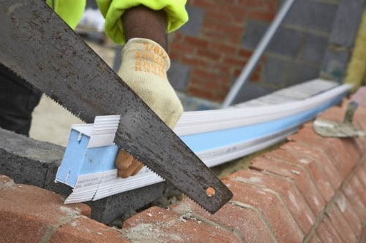 Bricklayer cutting insulation panel for cavity wall. : Stock Photo