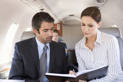 A businessman talking to his PA on a plane : Stock Photo