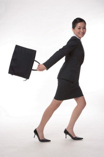Young woman in business suit, carrying briefcase, running : Stock Photo