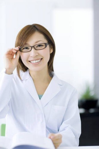Stock Photo: 4029R-254419 Woman in lab coat doing research