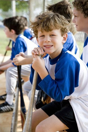 Stock Photo: 4029R-255099 Boy sitting on bench with youth league baseball team