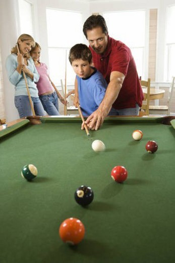 Family Playing Pool in Rec Room : Stock Photo