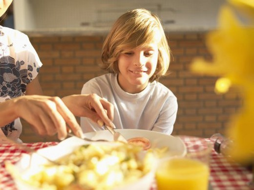 Stock Photo: 4029R-256589 Mother helping son with food