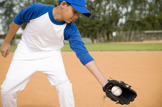 Boy catching baseball in glove : Stock Photo