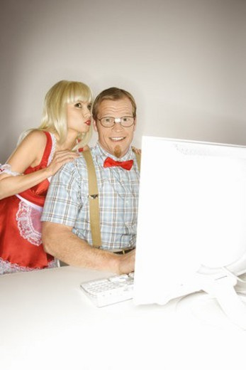 Caucasian young blonde woman dressed in french maid outfit whispering to Caucasian young man sitting behind computer dressed like nerd. : Stock Photo