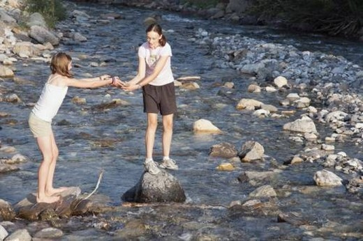 kananaskis country, alberta, canada; two girls playing on the rocks in the river : Stock Photo