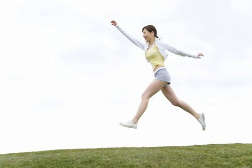 A Young Woman Jumping on the Grass, Low Angle View, Side View : Stock Photo