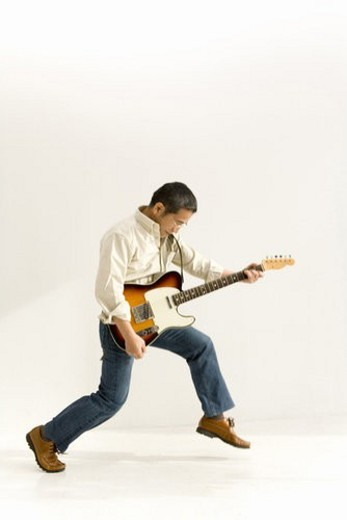 A Mature Adult Man Playing a Guitar, Side View : Stock Photo