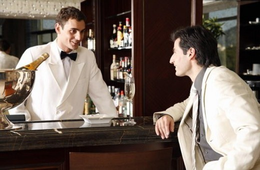Man sitting at a bar talking to the bartender : Stock Photo