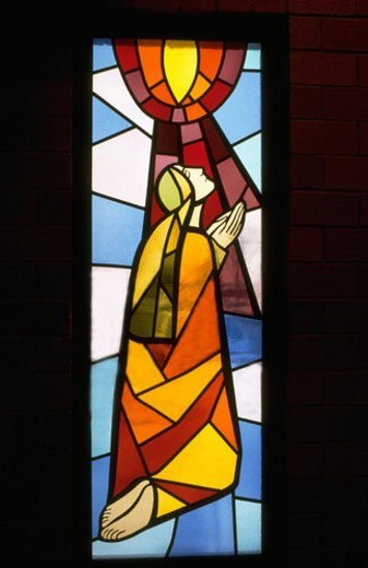 Stained glass window with Mary praying : Stock Photo