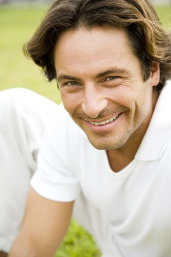 Portrait mid adult man sitting on the grass : Stock Photo