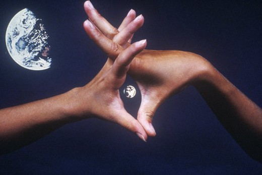 Special effects composite of interlaced hands and Earth in black sky : Stock Photo