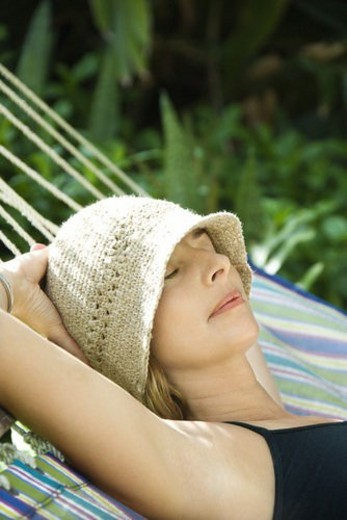 Caucasian mid-adult woman napping in hammock. : Stock Photo