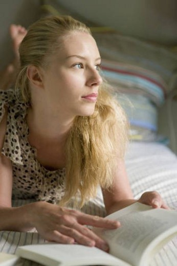 Woman holding a book and lying on bed, looking away, front view, differential focus : Stock Photo