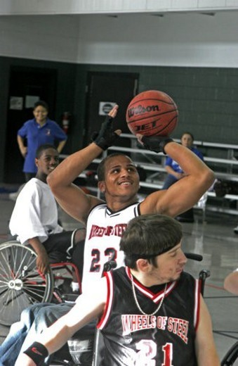 Teenage boy in wheelchair shooting a basketball as a young boy in wheelchair tries to block the ball. : Stock Photo