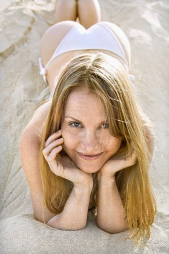 Portrait of pretty redheaded female lying in sand wearing bikini. : Stock Photo