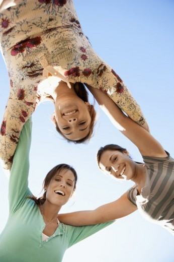 Three young women huddling (directly below) : Stock Photo