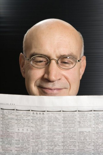 Head shot of Caucasian middle-aged businessman reading newspaper. : Stock Photo