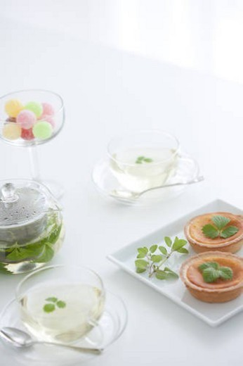 Herbal tea, a glass of candy and tarts : Stock Photo