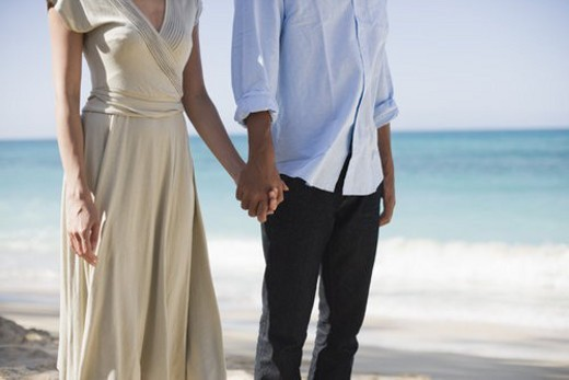 Stock Photo: 4029R-267887 Midsection of a couple standing at beach