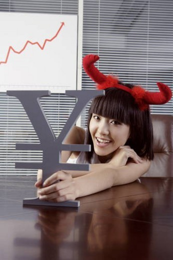 Stock Photo: 4029R-270296 Young woman wearing two red horn, holding RMB symbol