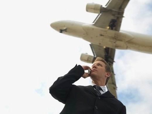 A Businessman Talking on a Cell Phone with an Airplane in the Background, Low Angle View, Waist Up : Stock Photo