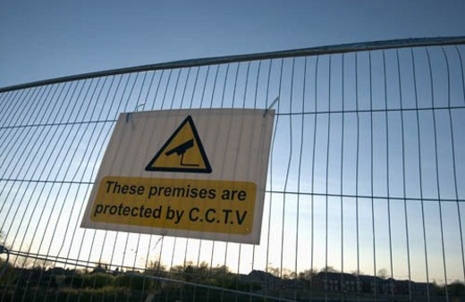Fence around a development site preventing public access with warning sign : Stock Photo