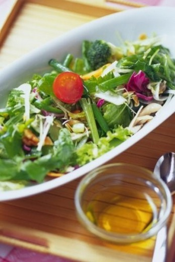 Stock Photo: 4029R-273764 Mixed salad leaves with glass on tray,  Differential Focus