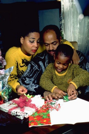 Stock Photo: 4029R-274463 Parents helping son wrap Christmas gifts