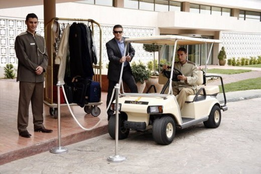 Stock Photo: 4029R-274652 Bellboy driving hotel cart