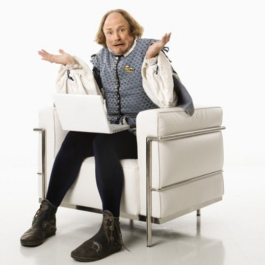 William Shakespeare in period clothing sitting on modern chair with laptop and shrugging with confusion at viewer. : Stock Photo