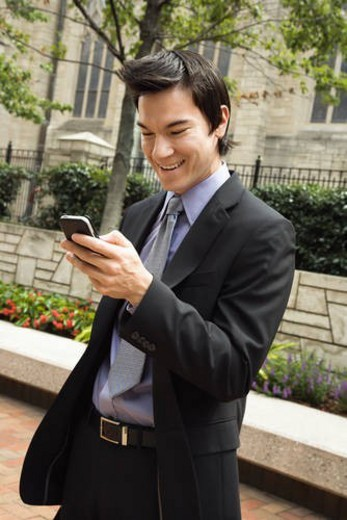 Stock Photo: 4029R-274986 Asian business man standing looking at cell phone messages smiling.