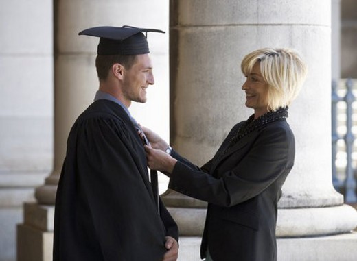 A mother checking her graduate son s gown : Stock Photo