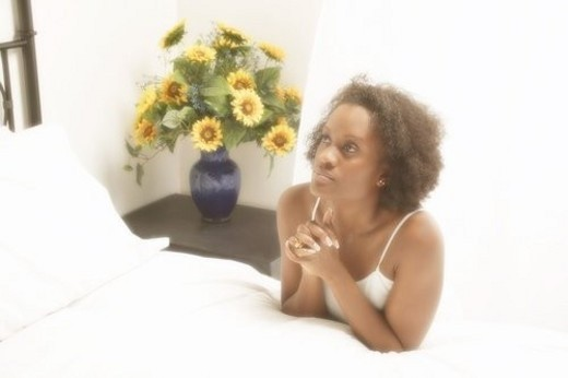 Stock Photo: 4029R-277107 Woman prays by her bedside