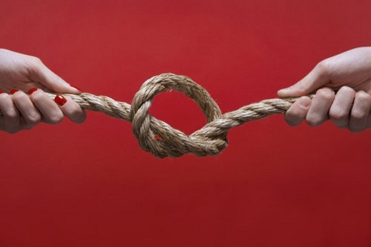 Stock Photo: 4029R-277287 Two hands tying knot (close-up)