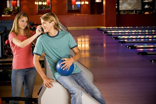 Teenage boy and girl in a bowling alley, talking on mobile phone : Stock Photo