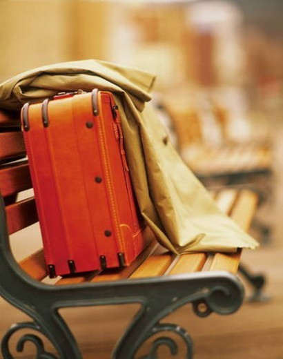 A suitcase and jacket waiting on a bench : Stock Photo