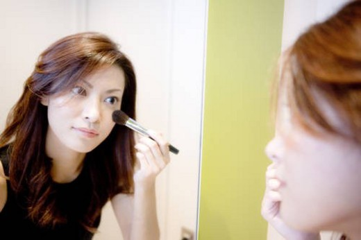 Young Woman Making Up, Looking at Mirror : Stock Photo