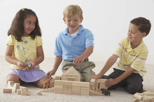 three children building noah s ark with wooden blocks : Stock Photo