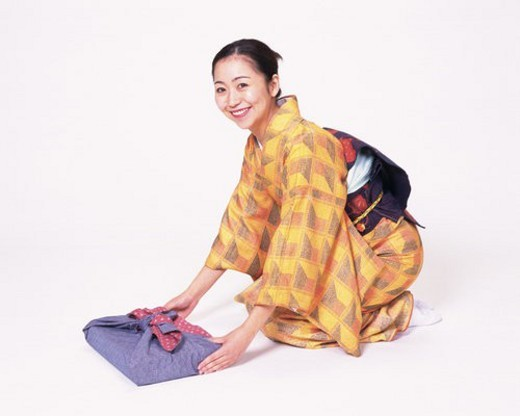 A woman in kimono sitting and holding a gift, High Angle View, Side View : Stock Photo