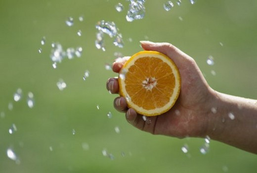A Hand With An Orange, And A Spray : Stock Photo