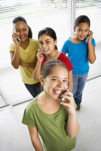 Stock Photo: 4029R-284372 Preteen girls of mutiple ethnicities talking on cell phones and looking at viewer.