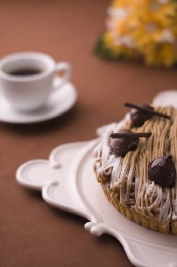 Stock Photo: 4029R-28500 Tart with chestnut cream and a cup of coffee, colored background