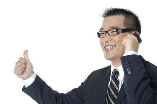 Stock Photo: 4029R-285139 Businessman talking on a mobile phone and showing thumbs up