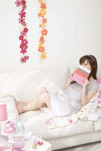 Stock Photo: 4029R-285383 Young woman holding book on sofa