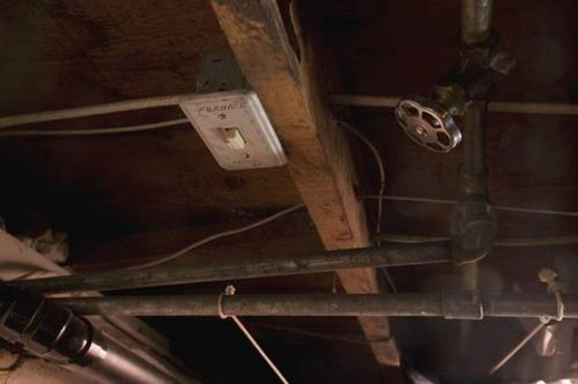 a furnace switch, valve and pipes in a ceiling : Stock Photo